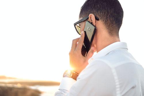 Mann der im Sonnenuntergang telefoniert
